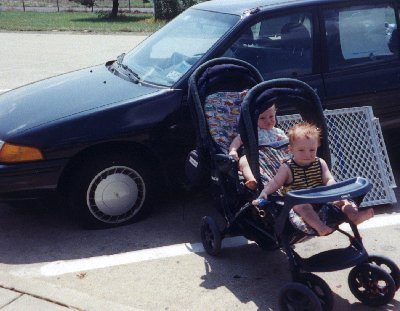 A picture of Katy's sons in a double stroller next to a flat tire