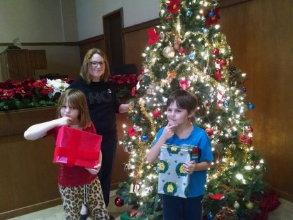 Children looking at presents by a lighted Christmas tree