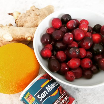 A bowl of cranberries, with ginger and orange and chipotle peppers